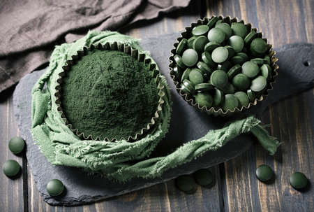 Spirulina tablets and powder in bowls on a wooden background