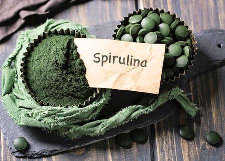 Spirulina-Tabletten und Pulver in Schüsseln auf einem hölzernen Hintergrund