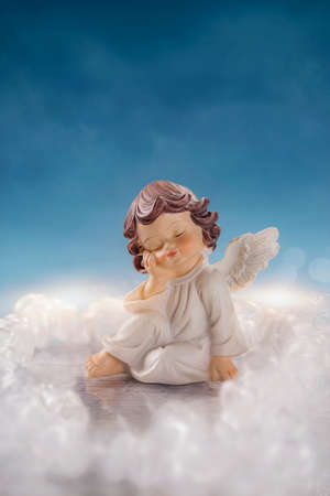 tombstones: Little angel sitting in the clouds Stock Photo