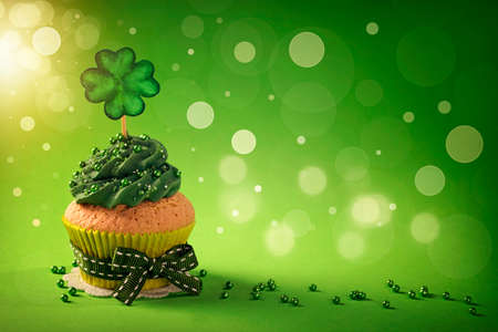 patrick: Cupcake with clover cakepick on a wooden background Stock Photo