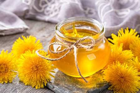 gold: Dandelion honey in a jar and fresh flowers