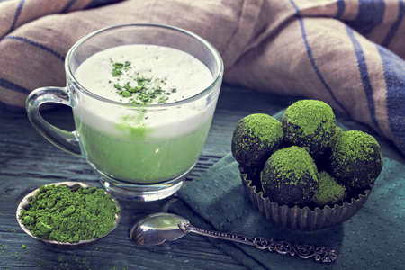 blue green background: Matcha energy balls from dates and almonds and matcha green tea latte