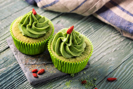 Matcha cup cakes on a wooden background