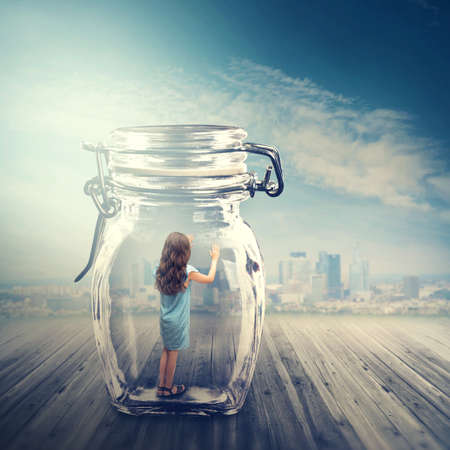 Young girl standing in a glass jar