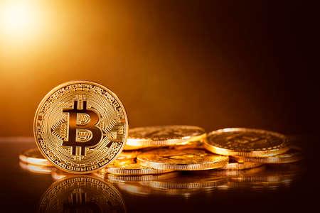 Gold bitcoins on a yellow background Фото со стока