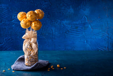 Yellow cake pops in a vase