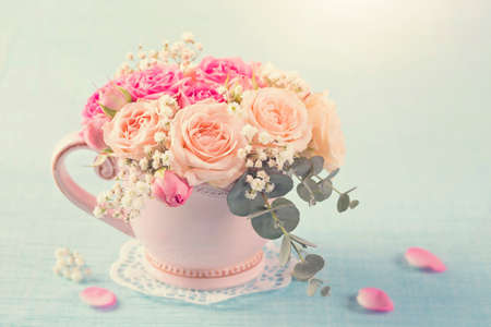 Pink roses in a teacup on a pastel blue background Stock Photo - 117585021