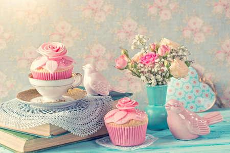 Cupcakes with pink flowers. Retro vintage still life. Banco de Imagens