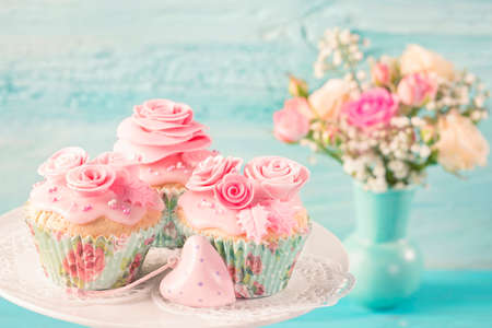 Cupcakes with pink flowers on a blue wooden background