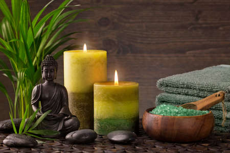 Buddha statue ,towels and candles on a brown background Stock Photo