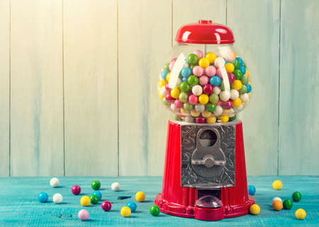 Carousel Gumball Machine Bank on a wooden background Stock Photo