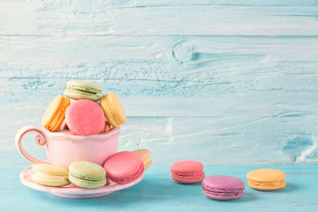 Colorful macarons in a cup on a blue wooden background