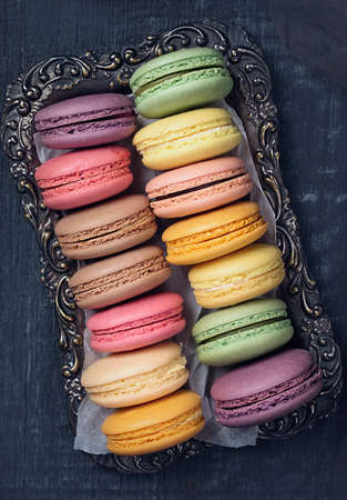 Colorful macarons on a dark wooden background