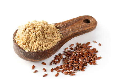 Linseed flour in a wooden spoon isolated on a white background