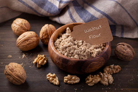 Walnut flour in the wooden bowl and whole seeds Standard-Bild