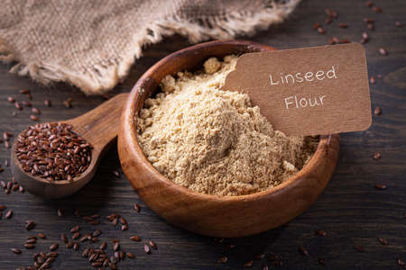 Linseed flour  in a wooden bowl isolated on a white background