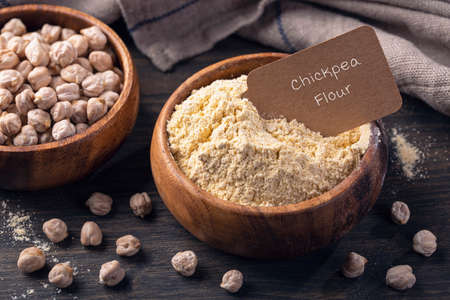 Chickpea flour in a wooden bowl  isolated on a white background
