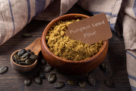 Pumpkin seed flour  in a wooden bowl  isolated on a white background