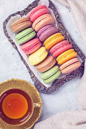 Colorful macarons and a cup of tea background