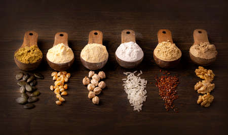 Gluten free flours in wooden spoons on a brown background
