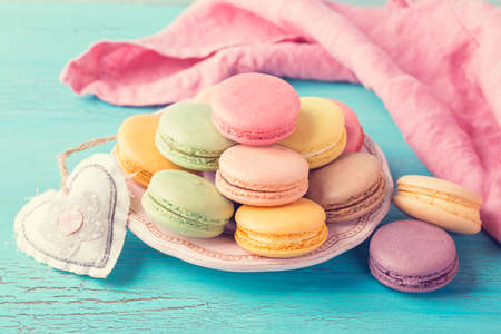 Colorful macarons and a cup of tee background