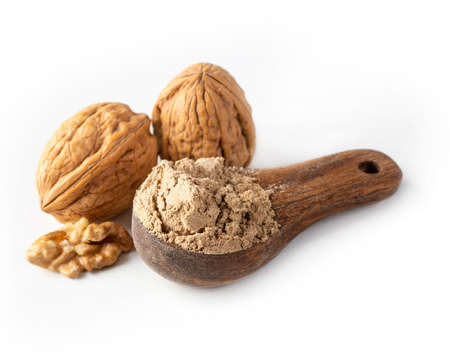 Walnut flour in the wooden spoon isolated on a white background
