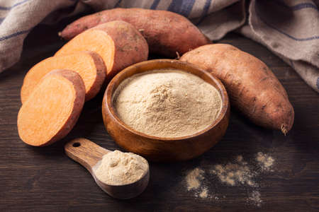 Sweet potato flour in a wooden bowl isolated on a white background