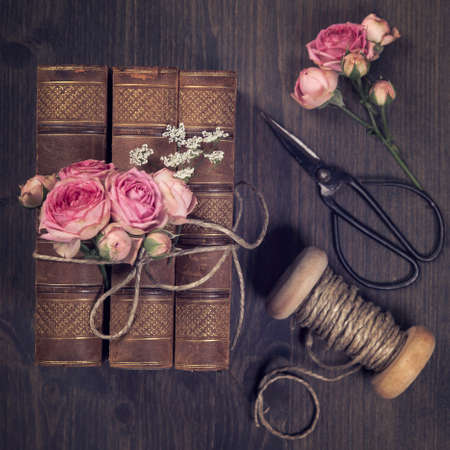Pink flowers and the old books on a brown background Standard-Bild - 148743205