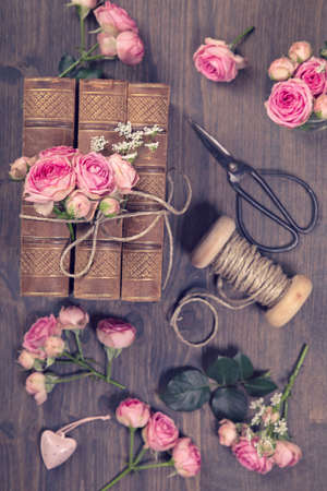 Pink flowers and the old books on a brown background Standard-Bild - 148290004