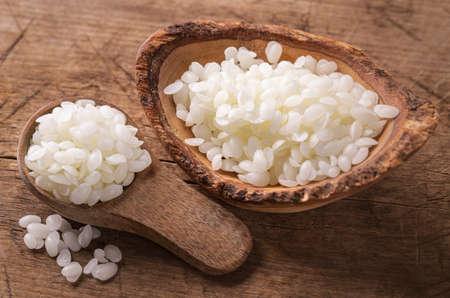 Beeswax pellets in the spoon Standard-Bild - 155839637
