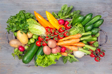 Vegetables in box on wooden background. Wooden note for your text. Standard-Bild