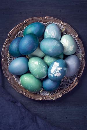 Natural dyed easter eggs on a wooden background. Colored with red cabbage. For greenish blue red cabbage with soda can be used.
