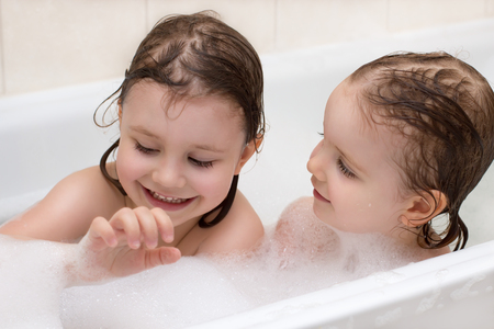 Two adorable little girls taking a bath with soap suds