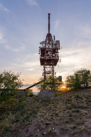 Transmitter tower antenna during the sunset on small hill.