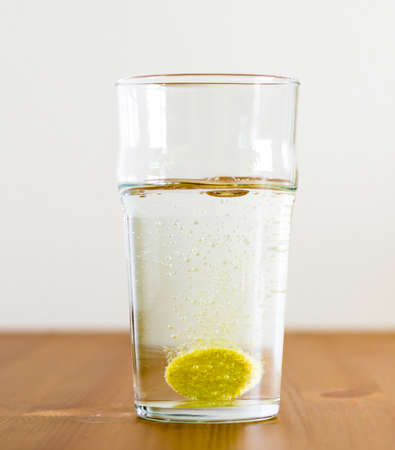 Effervescent tablet and glass of water. Vitamin beverage Imagens