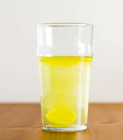 dissolve: Effervescent tablet and glass of water. Vitamin beverage Stock Photo