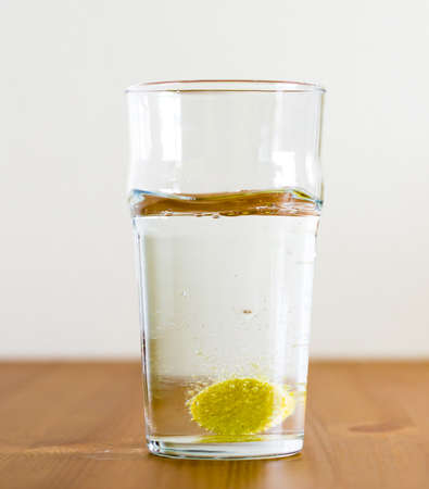 Effervescent tablet and glass of water. Vitamin beverage Stock Photo