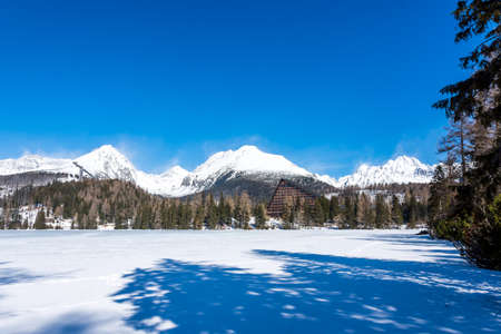 Slovakia, Strbske Pleso: View of frozen lake in Big Tatra, Slovakia. Mountains in background, the trees and lake in foreground. Winter and snow, Sport vacation and tourism.