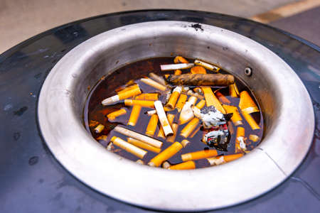 Closeup view of cigarette trash on top of recycle bin. Cigarettes are in water. Disgusting unhealthy trash and garbage