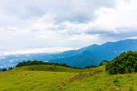 Panoramatic view to Slovenia Alps near city Kamnik. Big plateau with pasture and wooden houses. Landscape with green grass and clouds above the hill Reklamní fotografie
