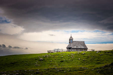 Church in the Slovenia big plateau pasture (Velika Planina). Chapel on the hill, religion symbol.Dramatic mystic clouds and colors. Green meadow and blue sky with clouds. Plateau near the Kamnik city. 免版税图像
