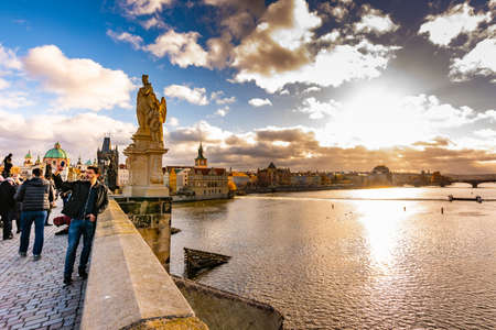 PRAGUE, CZECH REPUBLIC - 1.12.2018: Tourist on Charles bridge is taking selfie photo near the Vltava river. Dramatic and magic clouds and sun