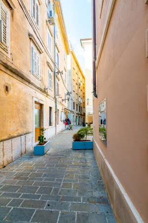 Old and narrow streets in Piran city, Slovenia. Ancient medieval streets in town center of famous European city, near the adriatic sea. Old houses with wooden windows and doors, magical atmosphere