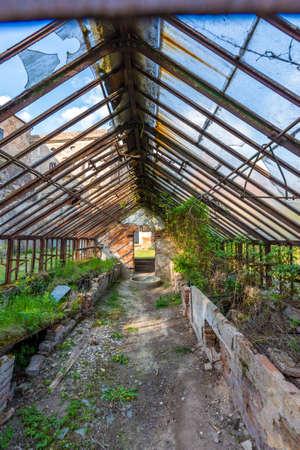 Look to old ruined greenhouse. Broken ancient greenhouse with broken windows. 写真素材