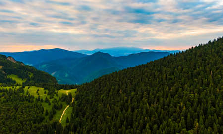 Aerial view to Mala Fatra mountains in Slovakia. Sunrise above mountain peaks and hills in far. Beautiful nature, vibrant colors. Famous tourist destination for hiking and trekking. Cloudy weather