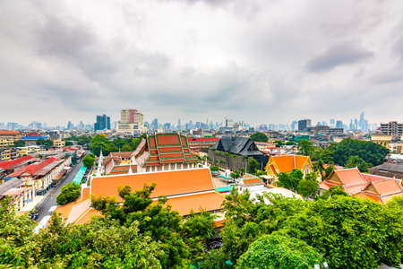 Panorama view of Bangkok city, Thailand. Cityscape of residental buildings in foreground, temples, skyscrapers and modern buildings in far. Fresh trees and plants. Cloudy weather, dramatic clouds