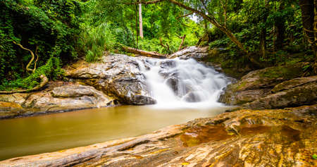 Beautiful waterfall Mae Sa, Thailand. Fresh and pure water stream is flowing on the rock stone ground in tropical rainforest. Fresh plants and trees above river. Vibrant colors in pure nature. 版權商用圖片