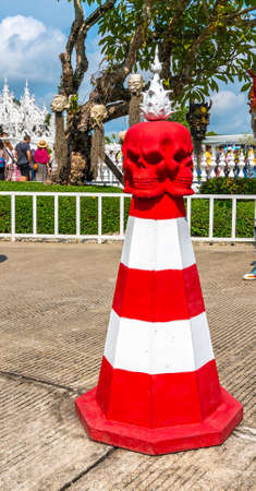 CHIANG RAI, THAILAND - 6.11.2019: Detail of red and white traffic cone in shape of skull head near the White temple (Wat Rong Khun). Devil symbology placed on the ground near famous buddhist temple.