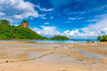 Panoramic view of east Railay beach, Krabi town, Thailand. View from the shadow of tree. Landscape with sand beach in foreground and huge limestone rocks in background. Summer day.