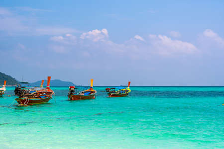 Long tail boat on the sea at Ko Lipe island, Thailand. Tropical island with white sand, beach and turquoise sea is part of Tarutao National Marine Park. Idyllic vacation, relaxation in paradise.